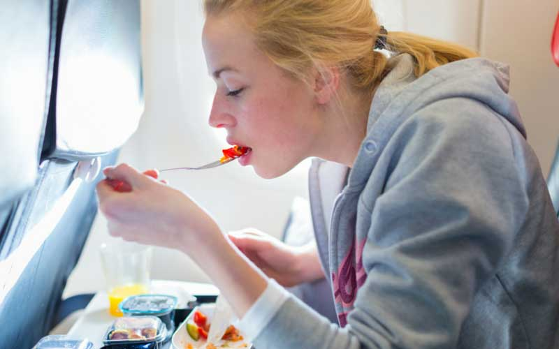 Girl eating meal on airplane.