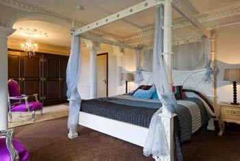Plush hotel four poster bed